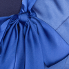 A close up of the bow on the bow jacket in blue