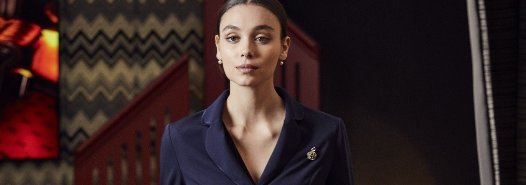A banner image of a model wearing a cropped blazer in navy