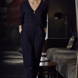 A model wearing a navy blue jumpsuit
