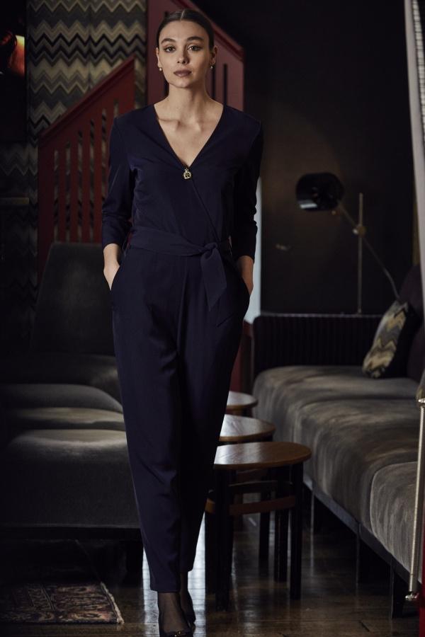 A model wearing a navy blue jumpsuit