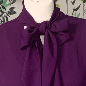 A pussy bow blouse in purple on a manequinn