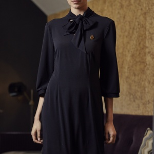 A model wearing a navy blue pussy bow dress