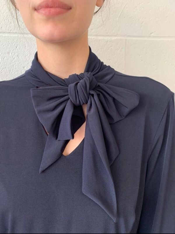 A close up of the bow on a pussy bow blouse in navy