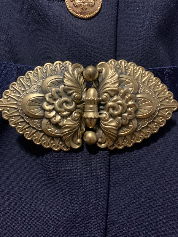 A close up of a gold belt clasp