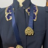 A gold belt clasp modelled on a mannequinn with a navy blue blazer