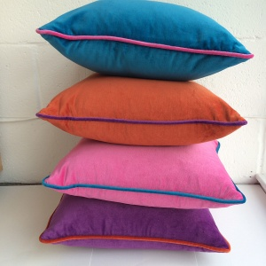 4 velvet cushions in different colours stacked on top of each other