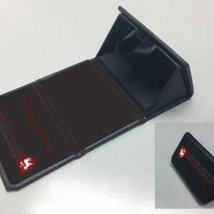 A triangular chaped cufflinks box in black with custom branding shown on the inside of the lid